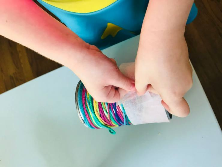 child taping tissue paper onto can
