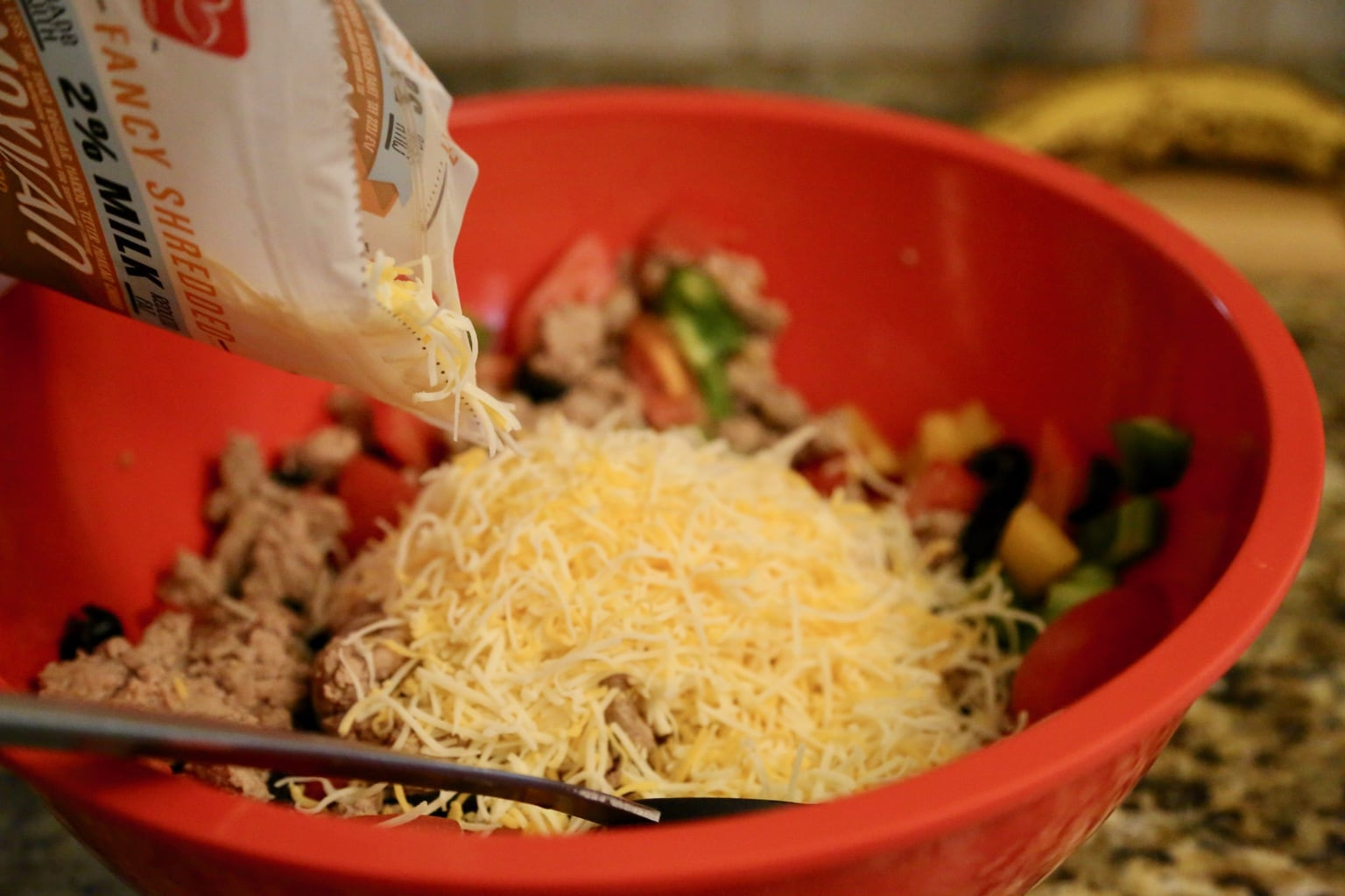 child pouring cheese into taco salad bowl