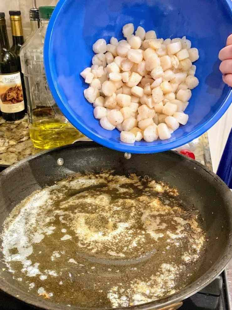adding raw scallops to pan