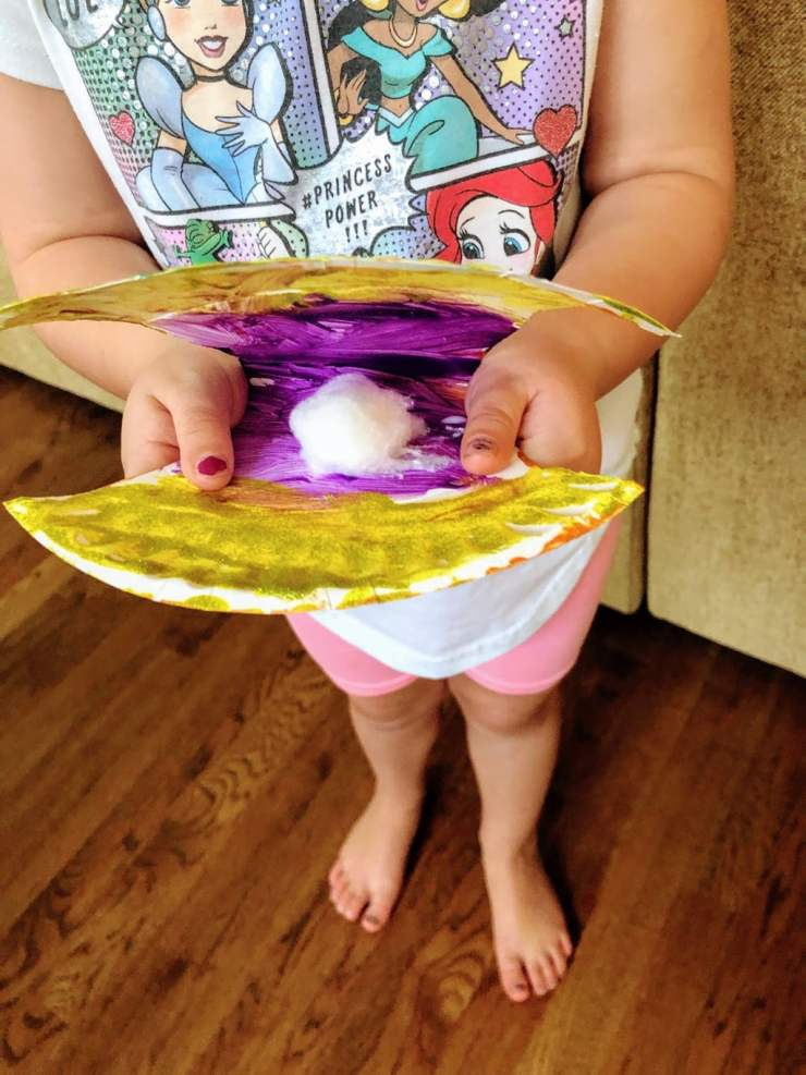 child holding open scallop craft