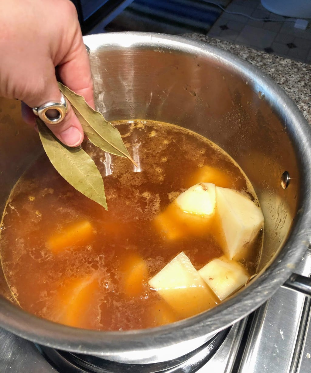 Adding spices to boiling broth for potato leek soup