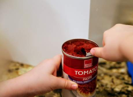 child scooping tomato paste out of can