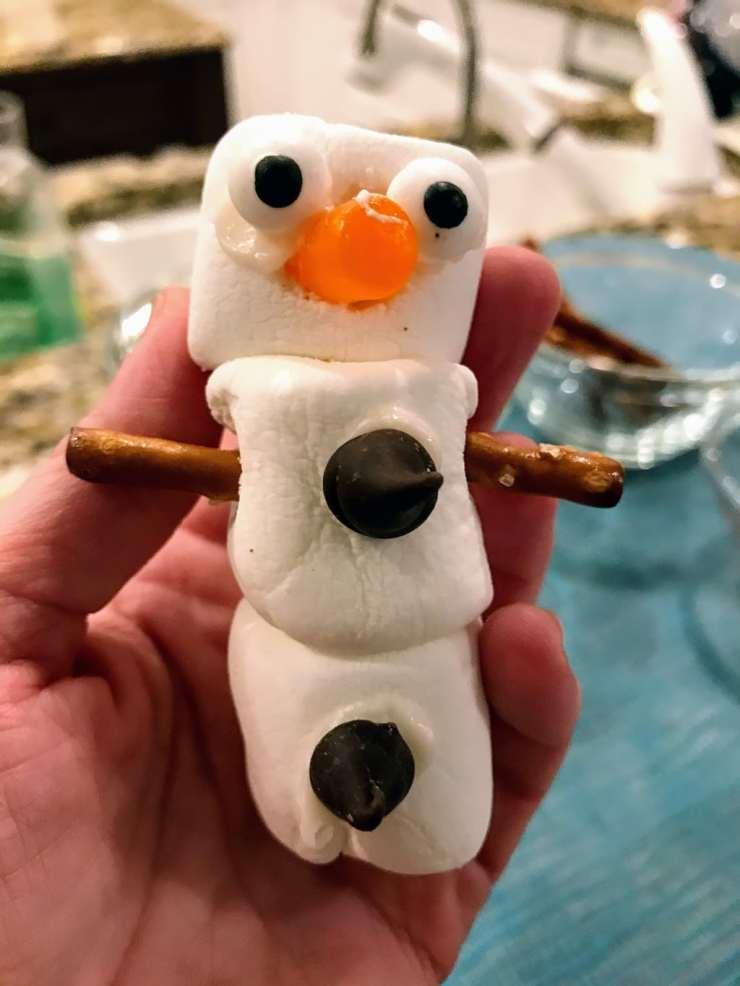 child holding marshmallow snowman