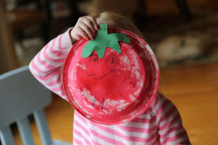 child holding Paper Plate Craft Sponge Art Tomato craft