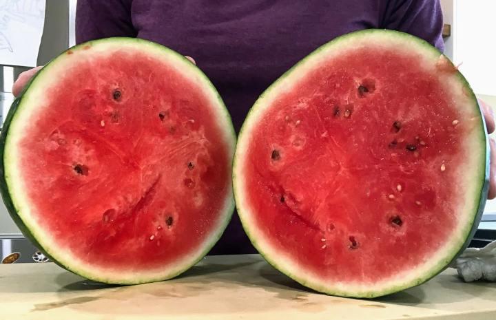 watermelon cut in half on cutting board