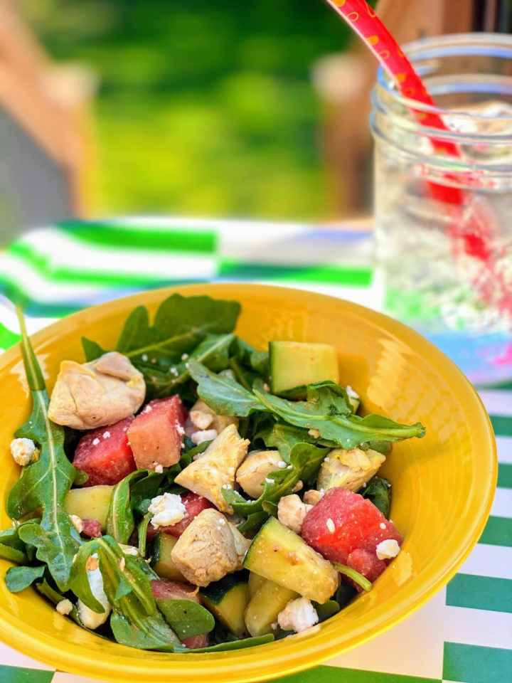 yellow bowl with watermelon salad, next to icy drink, on green and white striped tray outside