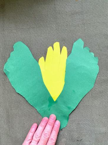 gluing green cutout footprints to yellow cutout handprint
