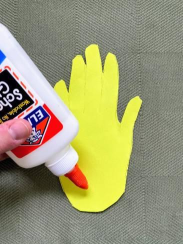 adding glue to yellow handprint cutout