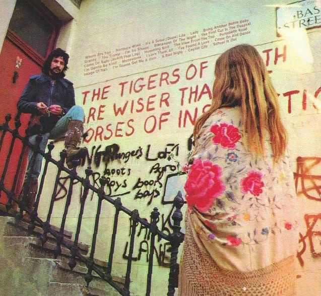 "Cat Stevens photographed by the William Blake graffiti ""The tigers of wrath are wiser than the horses of instruction"" on the corner of Lancaster Road and Basing Street in London (1970)."