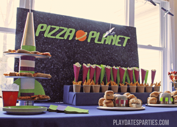 "This Toy Story party includes a buffet themed around the original movie's ""Pizza Planet"", including a rocket ship pizza platter and UFO platters."