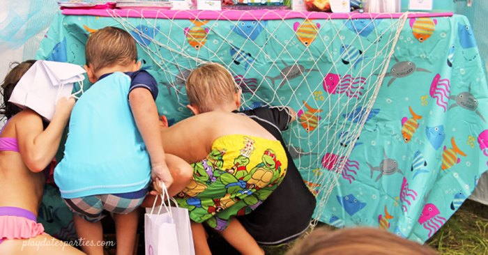 A picture of kids looking under a table at a party for kids treasure hunt ideas.
