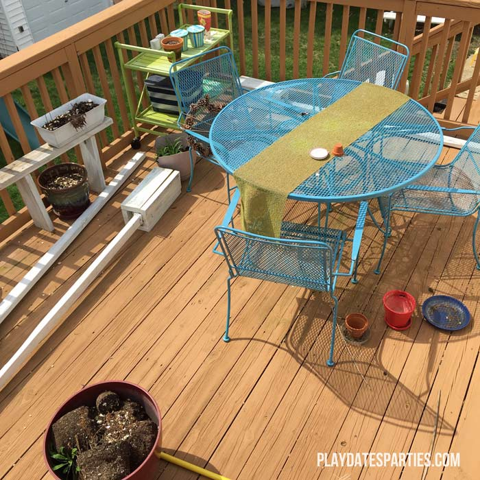 Picture of a deck with a bright blue patio set, green serving cart, and patio boxes.