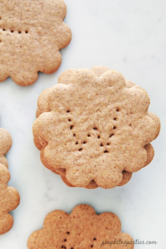Flower-shaped homemade graham crackers with letters pierced into them