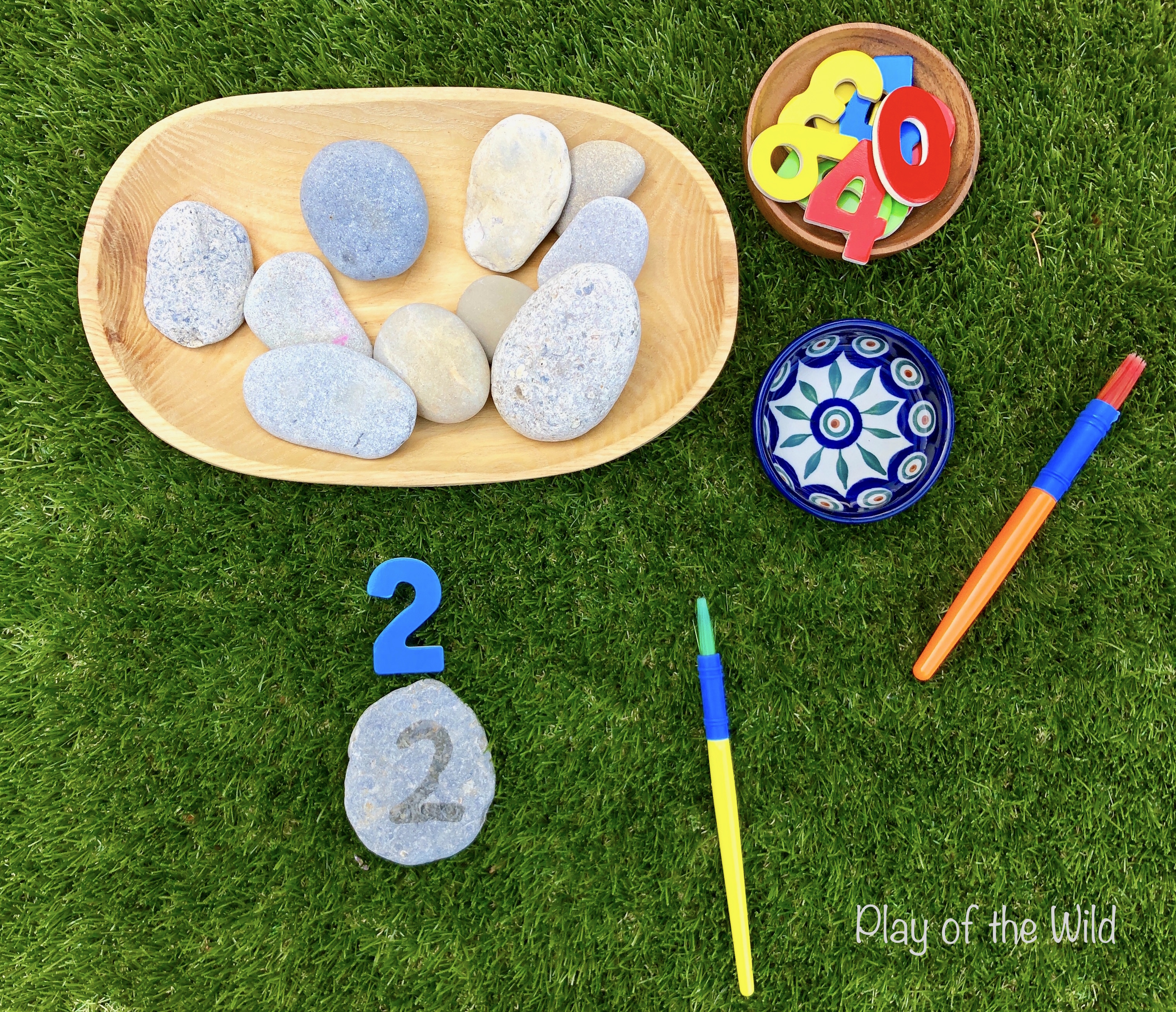 Practicing Writing Numbers 1 - 10 with rocks and water.