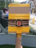 photo of a box shaped camera with a cardboard tube lens through the middle. It is held together with yellow duct tape.