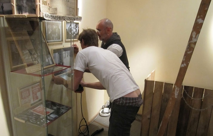 "Founder and proprietor of the Ramones Museum Florian ""Flo"" Hayler, in industrial-strength saggies, works with Arturo in getting the display of over 100-plus photos into precise and perfect position."