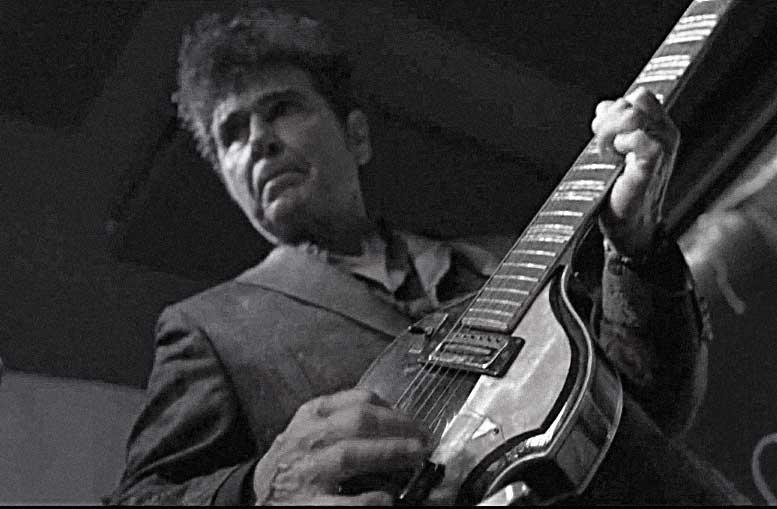Tav Falco playing guitar