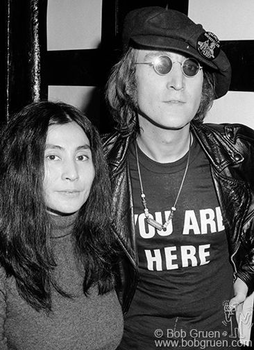 John Lennon with 'You Are Here' shirt and Yoko Ono at the Attica Benefit at The Apollo, NYC. December 17, 1971 © Bob Gruen www.bobgruen.com