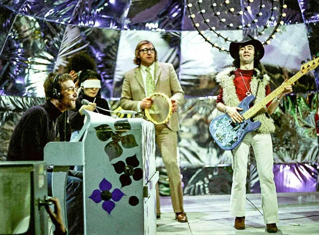 BP Fallon (bass guitar/hat) in John Lennon & The Plastic Ono Band 1970. L to r: John Lennon, Yoko Ono, Beatles' tour manager Mal Evans & BP Fallon. Photography courtesy of Guitar Magazine