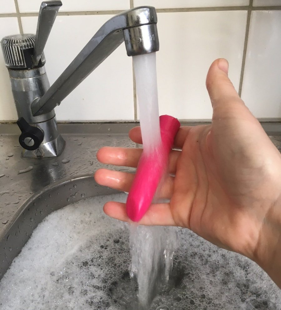 A hand cleaning a sex toy by holding a pink bullet vibrator under a stream of water from a tap