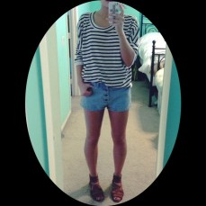 Striped breton top tucked into light wash, high-waisted shorts and sandals.