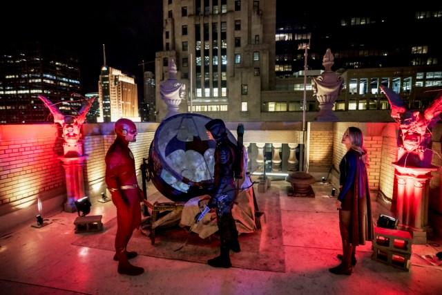 Flash (Stephen Amell), Green Arrow (Grant Gustin) y Supergirl (Melissa Benoist) descubren la Batiseñal en Elseworlds. Imagen: Parrish Lewis/The CW.