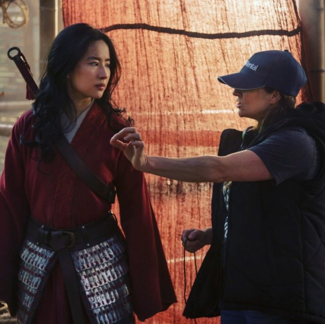 Yifei Liu como Mulán y la directora Niki Caro en el set de Mulan (2020). Imagen: Mulan Twitter (@DisneysMulan).