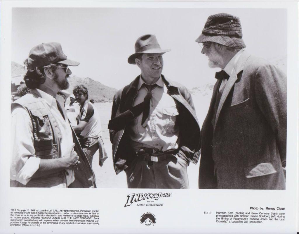 """El director Steven Spielberg, Harrison Ford como el Dr. Henry Walton """"Indiana"""" Jones Jr. y Sean Connery (1930-2020) como el Profesor Henry Walton Jones Sr. en el set de Indiana Jones and the Last Crusade (1989). Imagen: Paramount Pictures/Lucasfilm"""