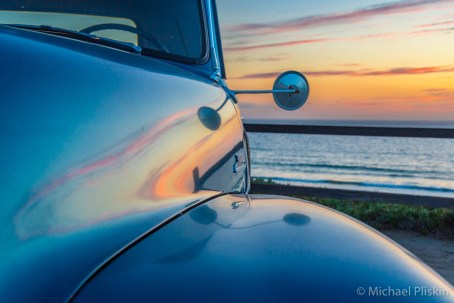 Sunset reflects in the fender of an early-50s Chevy pick-up truck.