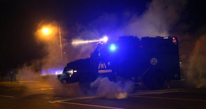 A tactical truck chases protesters down the street, shooting tear gas on W. Florissant Avenue in Ferguson, Mo. on Sunday afternoon, Aug. 17, 2014, after protesters throw rocks and bottles towards the police. (J. B. Forbes/St. Louis Post-Dispatch/MCT)