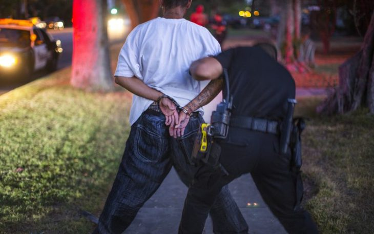 A San Bernardino Police police officer searches an alleged burglar suspects with gang affiliations on July 29, 2016 in San Bernardino, Calif. (Gina Ferazzi/Los Angeles Times/TNS)