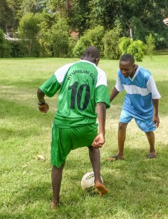 Mungai and Reagan modeling the new team sports jersys for the village football, volleyball and basketball teams.