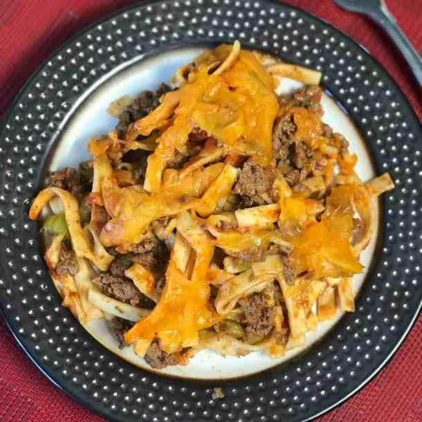 Plate of cheesy hamburger casserole recipe with noodles on a red placemat