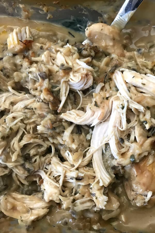 No-Peek Chicken in casserole dish with chicken breasts, Uncle Ben's wild rice, cream of mushroom soup, cream of celery soup and onion soup mix.