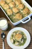 Plate of chicken and dumplings casserole next to full dish and glass of milk