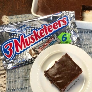 3 Musketeers Cake in a 9 x 13 pan next to 6 pack of 3 Musketeers Bars
