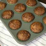 Baking pan of Bran and Raisin Molasses Muffins on white towel