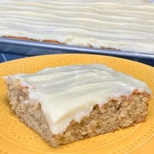 Square frosted Banana Bars on a yellow plate