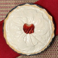 Whole Peanut Butter Pie directly over head on a red dish towel garnished with a strawberry in the center