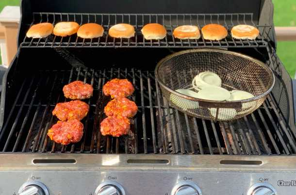 taco burgers, vegetables and buns on a gas grill