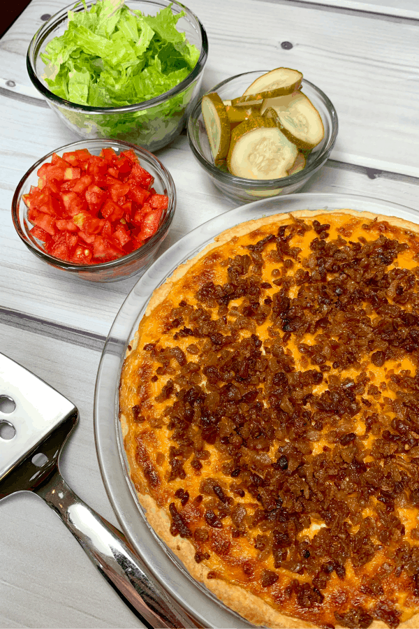 bacon cheeseburger pie garnished with tomatoes, lettuce and pickles