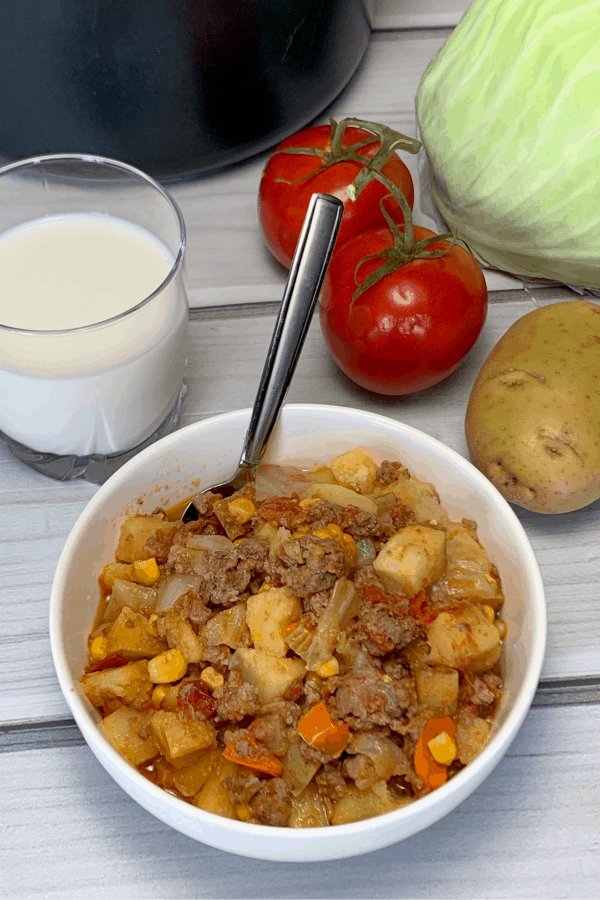 homemade veg and beef soup in a bowl next to tomatoes, potatoes and cabbage