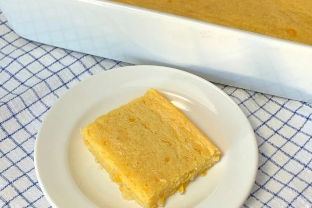 piece of basic corn casserole on a white plate sitting on a blue and white napkin