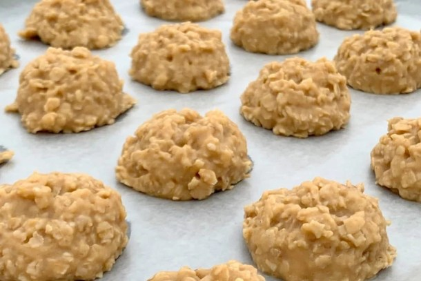 The best no-bake peanut butter drop cookies on a wax paper lined cookie sheet