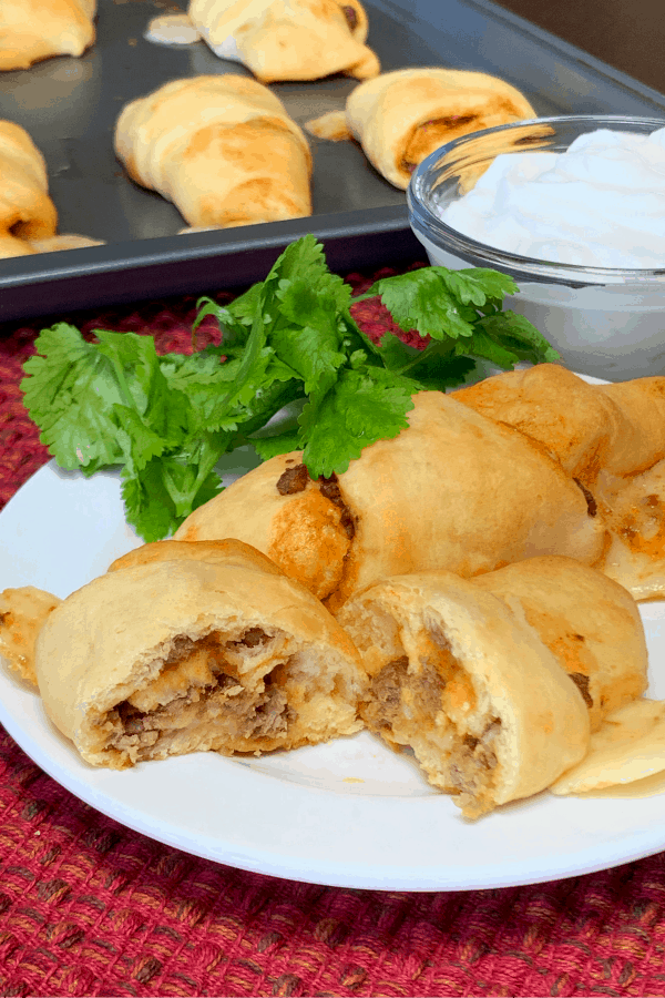 Tray of fresh baked handheld taco crescents next to plate with taco crescent cut in half and garnished with cilantro and sour cream