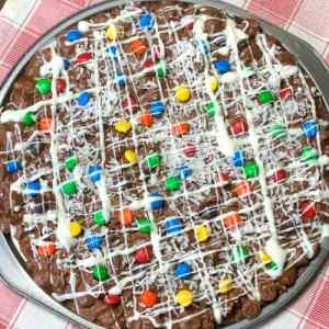 candy dessert pizza drizzled with white chocolate and sprinkled with M&Ms and coconut