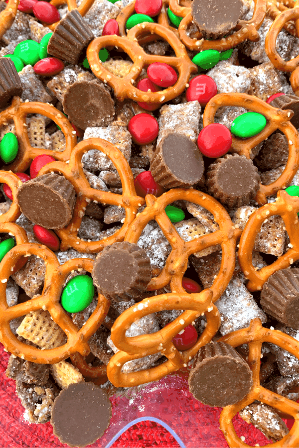 Confectioners sugar covered chex cereal, mini reeses cups, M&Ms and pretzels make Christmas Puppy Chow