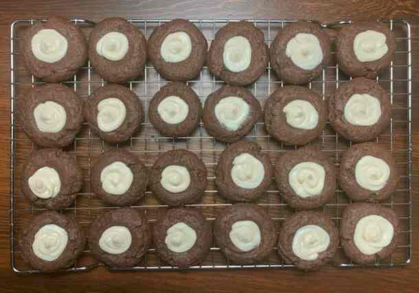 24 Chocolate thumbprint cookies filled with icing on a cooking rack on a wood table