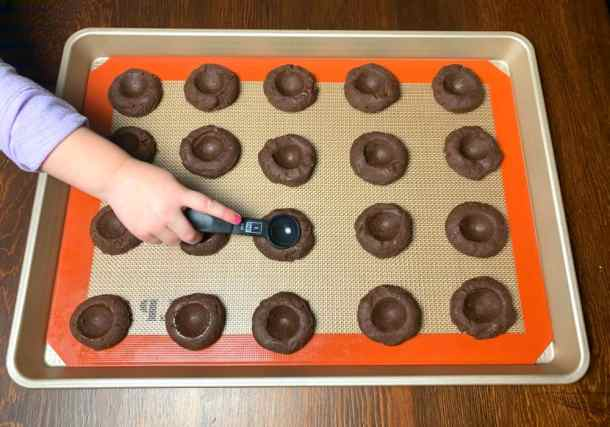 Hand using a teaspoon to shape wells in the center of chocolate thumbprint Christmas cookie dough