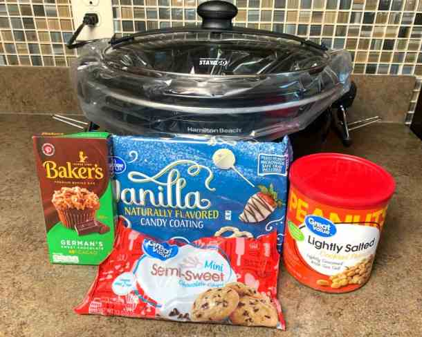 4 ingredients needed to make chocolate covered peanut clusters sitting in front of slow cooker - German chocolate, semi-sweet chocolate chips, white almond bark & peanuts